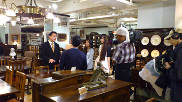 A shooting scene at the antique-interior selling shop, GEOGRAPHICA. The person on the left is the member of the staff, Mr. Hiroshi Ninagawa, who provided the program some fluent English commentary.